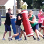 The North Iowa Football team is on the practice field, practicing tackling with red and blue guards.