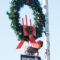 Zac Ree moves wires behind a one way road sign, a large wreath strapped to the light pole above him.