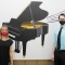 Arin and Mr. Arensdorf stand apart with a piano mural separating them. Both wear fabric masks.