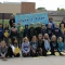 """Fourth graders line up in two rows, dressed in blue and holding yellow emoji faces. Three adults stand behind, holding a banner that reads """"4-ever a Bison."""""""