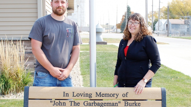 """Zac and Carolyn stand behind a tan bench. The bench is engraved, reading """"In Loving Memory of 'John The Garbageman' Burke. Jan. 11, 1993 - Aug. 18, 2020."""""""
