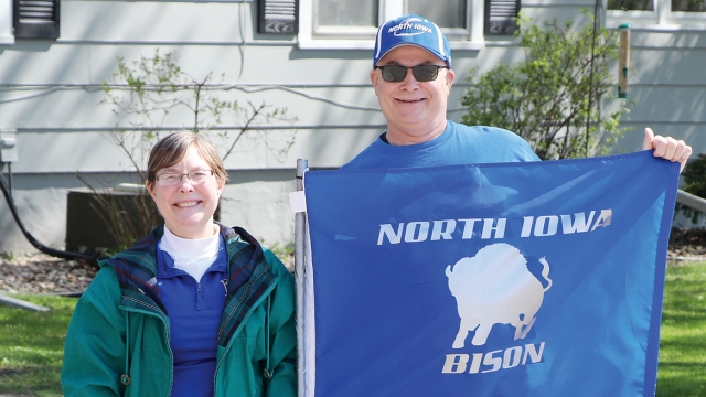 """Loree and Brad both wear blue and smile at the camera as Brad holds a blue flag saying """"North Iowa Bison"""" with a bison graphic on it."""