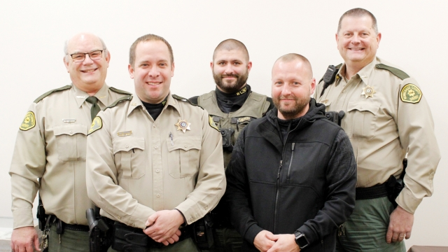 Five men stand in two rows, all balding or close-shaved and most wearing police uniforms.