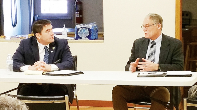Rep. Henry Stone and Sen. Dennis Guth talk to each other while sitting at a folding table.