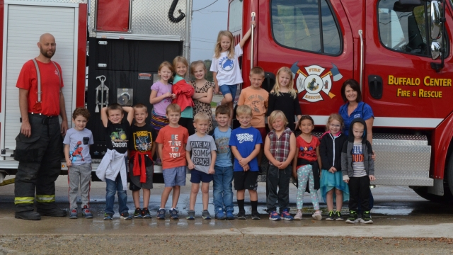 A firefighter with his overalls stands with a class and their teacher in front of a red fire truck.